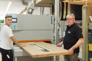 Werner Hartung (rechts) und sein Sohn Christian legen einen Haustürblattrohling in die neue Breitbandschleifmaschine ein