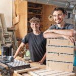 Johannes Müller (rechts) neben seinem Bruder Markus. Links die Hand-CNC Origin von Shaper Tools, die die komplexe Produktion des Möbels ohne CNC ermöglichte