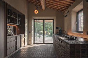 Rechts der Kochblock aus handgeformtem Cotto; links die Küchenzeile aus Mooreiche. Die Einbaugeräte sitzen hinter den Fronten Foto: Oliver Jaist