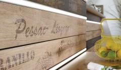 LED-Lichtleisten zwischen den mit Schriftzügen bedruckten Fichtenholzplatten betonen den Kontrast zwischen modernem Design und dem Vintage-Look der Holzoberflächen