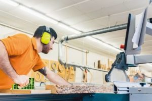 Carpenter_cutting_board_with_table_saw_in_his_workshop
