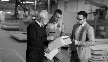 Portrait_of_three_men_standing_and_discuss_in_furniture_factory