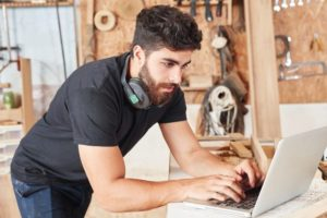 Junger_Mann_als_Programmierer_am_Laptop_Computer_online_im_Handwerker_Betrieb