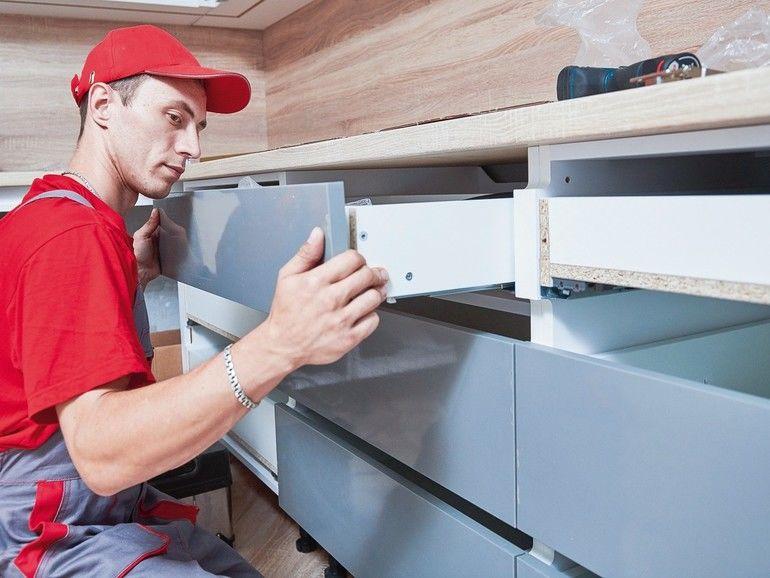 kitchen_installation._Worker_assembling_furniture_set._mounting_cabinet_lifting_mechanism