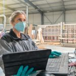 Woman_engineer_operating_on_a_industrial_digital_machine_and_wearing_protective_mask_against_coronavirus