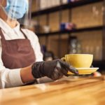 Unrecognized_female_cafe_worker_holding_a_cup_of_coffee_on_a_plate_and_placing_it_on_a_bar_counter