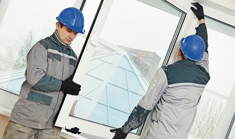 Two_male_industrial_builders_workers_at_window_installation