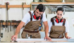 Carpenter_and_apprentice_working_together_in_workshop