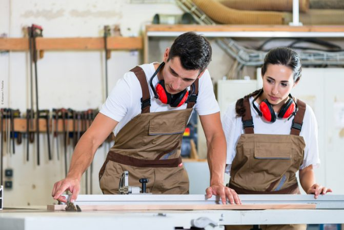 Carpenter_and_apprentice_working_together_in_workshop