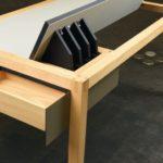 Gestaltete Gesellenstücke Baden-Württemberg 2020: Unterstützt durch einen Farbkontrast, zeigt der Schreibtisch eine ablesbare Gliederung in Gestell und seitlich eingeschobenes Korpuselement. Der Korpus übernimmt die Grundform des Trapezes und hält zwei Öffnungsfunktionen bereit: rechts vom Gestell schiebt sich die Korpushülle nach vorn und gibt von oben und linksseitig Stauraum frei. Frontal öffnet ein klassisch geführter Schubkasten mit Geheimfach in seiner Verlängerung. Der hintere Bereich der Platte kann auf Druck schräg gestellt werden und dient mit einer Magnetleiste als Stütze für ein Tablet. Die komplexen Öffnungsfunktionen verschmelzen mit einer wachen äußeren Form. Philipp Braunschweig, Schreinerei Braunschweig, 88605 Meßkirch-Rohrdorf. Erster Preis Gute Form Baden-Württemberg 2020. Fotos: Markus Dollenbache
