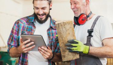 Senior_and_young_carpenter_working_at_workshop_using_digital_tablet