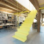 Sanierung eines Baudenkmals: Selbstbewusst gelb: Unterzugverstärkung und Treppe werden im Architekturbüro durch den Einsatz von Farbe ‧visuell zu einer Einheit zusammengezogen und können als visitenkartengleiches Statement gesehen werden