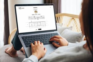 Mockup_image_of_a_woman_working_and_typing_on_laptop_computer_with_blank_screen_while_sitting_on_a_sofa_at_home