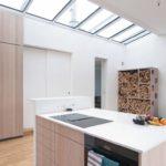 Dachwohnung-Innenausbau von Abitare Tischlerei: Die Silestone-Arbeitsfläche der Kücheninsel faltet sich auch über den auf Stahlprofilen angesetzten Tresen Fotos: Maria Jauregui Ponte