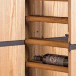 Rundholzstäbe nehmen im Auszug des hochbeinigen Weinschranks Flaschen unterschiedlicher Durchmesser auf