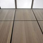 Dachwohnung-Innenausbau von Abitare Tischlerei: Die Paneelwand mit flächenbündigen Durchgängen, Spiegeln und Stauraum nimmt das Raster des durchgehenden Oberlichtes auf Fotos: Maria Jauregui Ponte