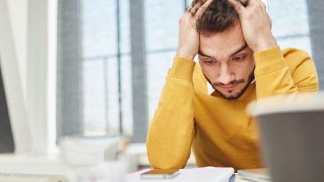 Mann_als_gestresster_Geschäftsmann_denkt_über_eine_Entscheidung_nach