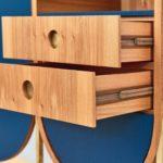 Das Highboard in Rüster mit ovaler gestreckter Front ist als Sammlerschrank konzipiert. Die elegante Formgebung stellt vor anspruchsvolle konstruktive und handwerkliche Herausforderungen: Die Aufrechten des Gestells aus Messingvierkantprofil gehen flächenbündig in den Korpus über, Schubkästen laufen auf präzise eingefrästen Vollholzkulissen in Nussbaum. Innenflächen sind in der Anmutung einer textilen Auskleidung blau lackiert. Die nach oben und unten begrenzenden halbkreisförmigen Segmente sind ungenutzter Raum, was sicherlich auch der begrenzten Fertigungszeit geschuldet ist. Ludwig Brand, design.s – Richard Stanzel, 85354 Freising-Pulling.Belobigung Gute Form Bayern 2020 Fotos: Studio Pfleiderer für dds
