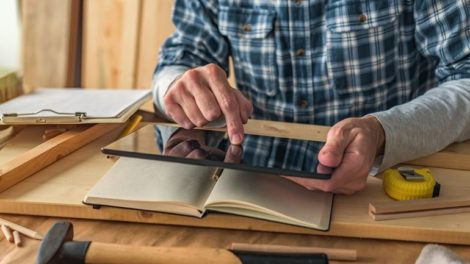 Carpenter_using_digital_tablet_to_complete_project_to_do_list_in_small_business_woodwork_workshop